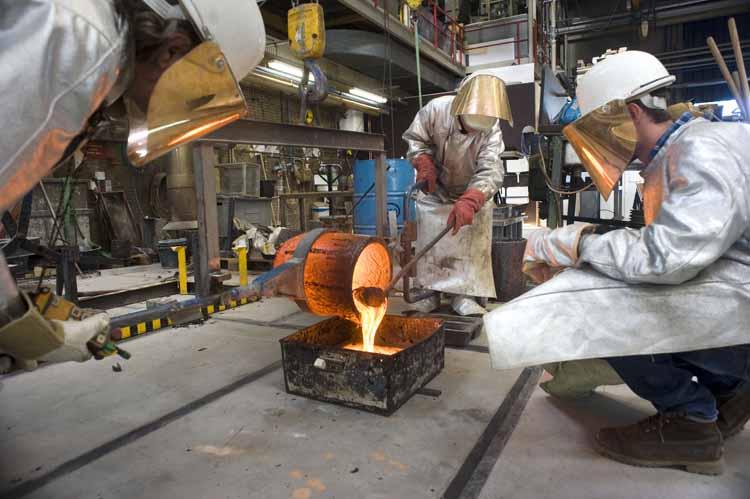 Vloeibaar basalt wordt gegoten in een mal. Jasper Rombouts (r.) en werkplaatsmedewerkers dragen speciale brandvrije pakken. foto Piet den Blanken