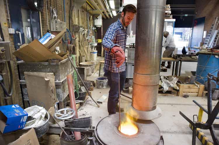 Jasper Rombouts, afgestudeerd aan de Design Academy in Eindhoven, controleert of het basalt is gesmolten. foto Piet den Blanken