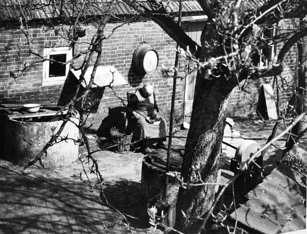 Mieke van Vroenhoven op haar erf, Best (Nieuwstraat), 1949. © Noud Aartsen | Brabant-Collectie, Tilburg University